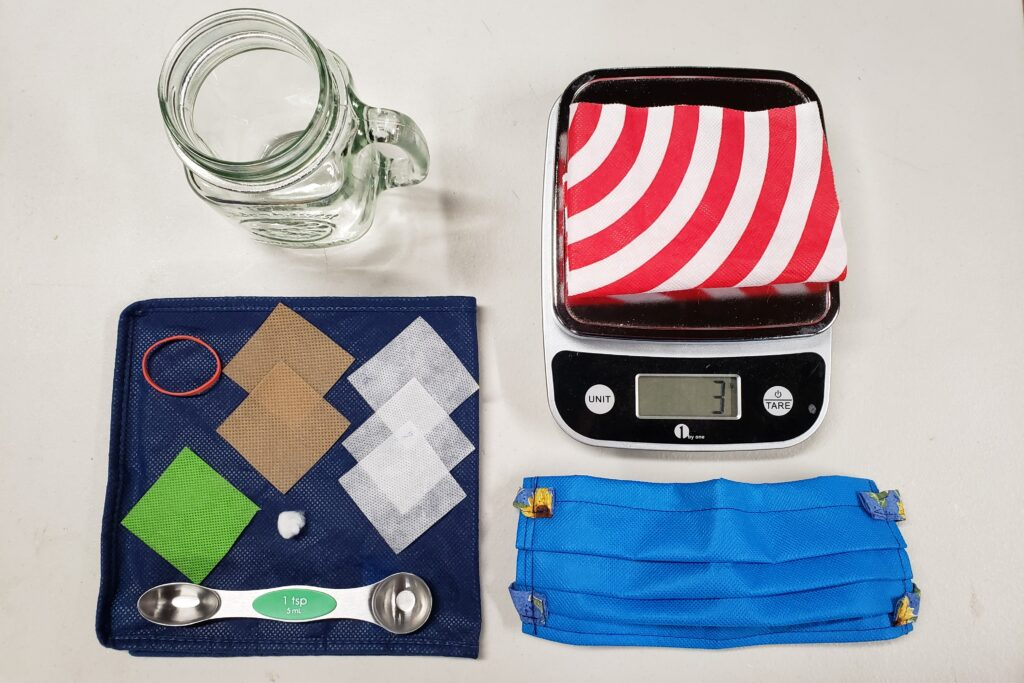 Photo: DIY Mask Testing Setup for Fabric Materials. Photo includes spunbond nonwoven polypropylene mask, teaspoons, scale, elastic band glass, and cotton ball