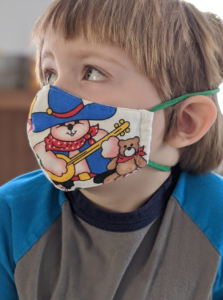 Masks for Children: Child wearing properly sized face mask with banjo bear print