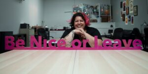 "Photo of Rachel Sadd, sitting at a table and smiling, with ""Be Nice or Leave"" in large pink letters highlighted as a banner in front of her. The color of the text matches the vibrant color of the pink streak in her hair"