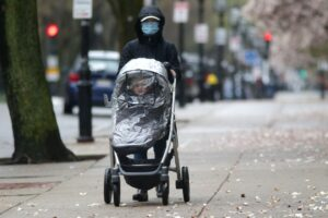 An adult wearing a mask pushes a covered stroller down the street on Commonwealth Avenue in Boston during the coronavirus pandemic. JONATHAN WIGGS/GLOBE STAFF