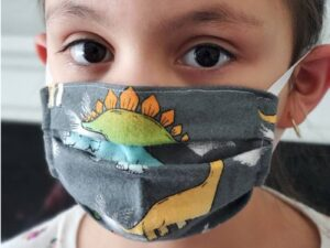 Fabric Masks for Children: Girl wearing a mask with dinosaurs on it