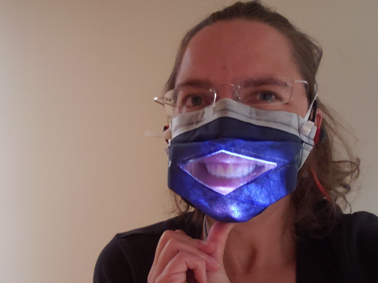 Photo of Dr. Songer in the MakerMask: Expression Glow Prototype: a window mask made with heat sealed seams and an internal light to improve visibility of the mouth in dimly lit situations.
